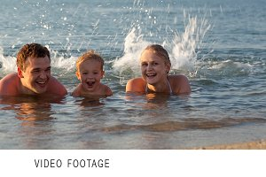 Young family splashing in the sea
