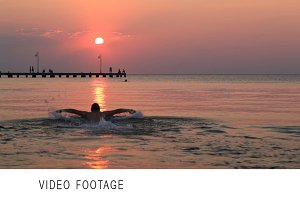 Man swimming in the sea at sunset