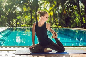 Beautiful young happy woman doing yoga exercise near swimming pool. Healthy lifestyle and good wellness concepts