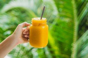 Mango smoothie in a glass Mason jar and mango on a green background. Mango shake. Tropical fruit concept