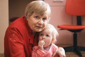 Portrait of a little sweet girl with her grandmother at home