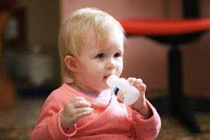 Baby girl toddler eats vitamins or pills at home