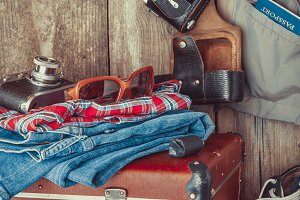 Old suitcase, clothes and camera