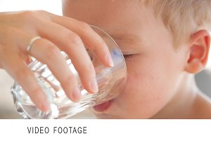Little boy drinkng a glass of fresh