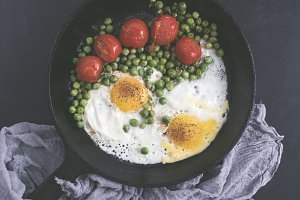 Fried eggs with tomatoes and peas