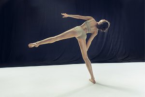 Young teen dancer ion white floor background.