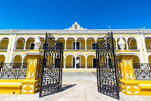 Gate and Yellow Colonial Building