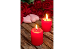 Two burning candles with fresh roses