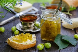 Green gooseberry jam on a wooden table