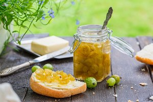 Green gooseberry jam in a jar on a wooden table