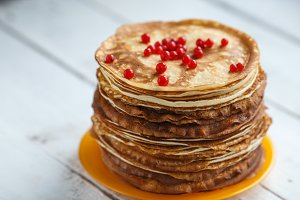 High stack of classic Russian thin pancakes with red currant. Rustic style. Traditional for the Russian pancake week Maslenitsa