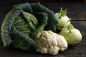 Savoy cabbage, cauliflower and kohlrabion a dark wooden table