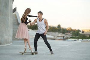 Ballerina on a skateboard. Guy helps