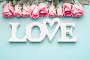 word LOVE with pastel pink roses
