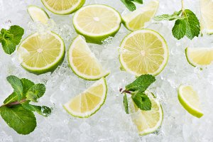 Juicy lime fruits on ice background.