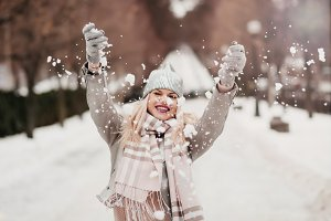 beautiful girl throws snow