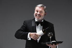 professional waiter in uniform is serving wine