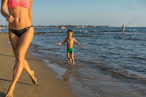 Boy with mother running to beach