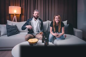 Couple watching TV sport at home