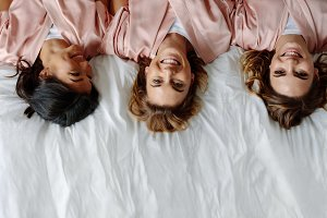 Three young women lying on bed