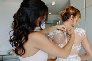 Bridesmaid dressing the bride