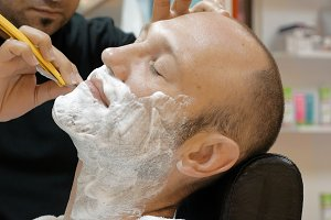 Barber is shaving his client in old fashion manner