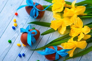 Easter background with decorative Easter eggs, narcissus and willow tree branch. Copy space, top view