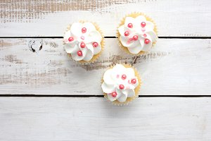 Cupcakes with sprinkles on wooden bg