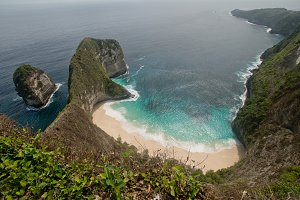 Rocky cliff with beach in the sea. Karang Dawa.