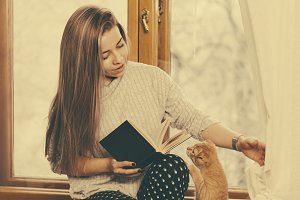 Girl read book and play with cat