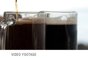 Pouring black beer into the beer cup