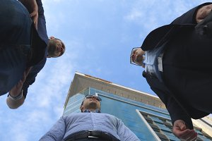 Low angle view of three business men standing outdoor near office and talking. Businessmen meet and speaking outside in the city with blue sky at background. Communication of happy colleagues. Closeup