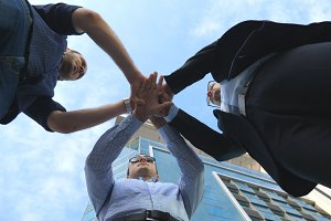 Three business men standing outdoor near office and stacked arm together in unity and teamwork. Hands of businessman team getting together in the center of a circle and then raised. Low angle of view
