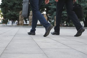 Feet of two businessmen walking in city street. Business men commute to work together. Confident guys being on his way to office. Legs of colleagues going outdoor. Slow motion Close up