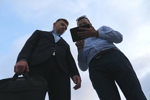 Two young businessmen talking and using tablet pc outdoor. Business men working on digital tablet outside with sky at background. Colleagues applying mobile technology. Low angle of view Slow motion
