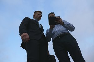 Two young businessmen meet, shake hands and talking outdoor. Business men using tablet pc outside with sky at background. Colleagues applying mobile technology. Low angle of view Slow motion
