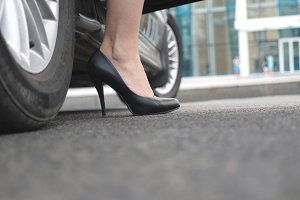 Legs of girl getting out of auto. Business man opens and holds the car door for the beautiful young woman in high heels shoes. Chauffeur opening door of automobile for female passenger. Close up