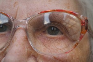 Old woman puts on glasses and looking into the distance. Granny wearing eyeglasses. Portrait of grandmother. Close up Slow motion