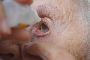 Old woman dripping medical drops in her eye. Portrait of grandmother. Healthcare and medical concept. Close up Slow motion
