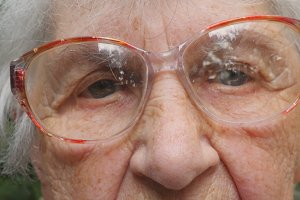Old woman in glasses looking at camera. Granny in eyeglasses spending time outside. Portrait of sad grandmother outdoor. Close up Slow motion