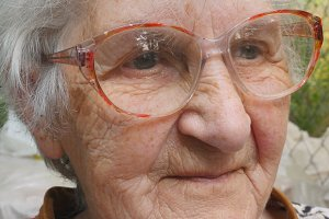 Old woman in glasses looking forward and smiling. Portrait of happy granny in eyeglasses spending time outdoor. Emotions of grandmother. Close up Slow motion