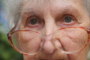 Old woman in eyeglasses turning her head and looking into camera. Granny wearing eyeglasses outside. Portrait of grandmother outdoor. Close up Slow motion