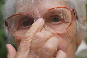 Old woman straightens her glasses and looking at camera outdoor. Portrait of sad grandmother with emotions and feelings. Granny wearing eyeglasses outside. Close up Slow motion