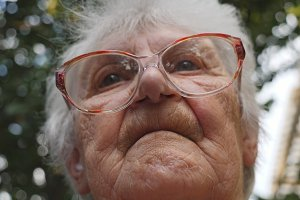 Old woman straightens her glasses and looking forward. Portrait of grandmother outdoor. Granny wearing eyeglasses outside. Low angle of view Close up Slow motion