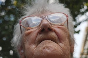 Old woman looking forward. Portrait of grandmother outdoor. Granny wearing eyeglasses outside. Low angle of view Close up Slow motion