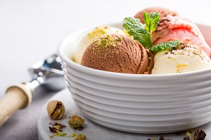 Assorted ice cream in white bowl.