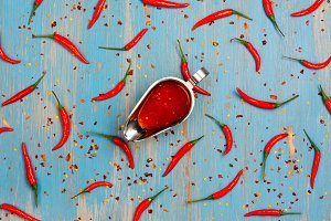 Abstract background with red hot chilli pepper pods, spicy sauce and flakes on blue
