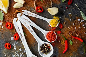 Dry herbs and spices in measuring spoons on white stone kitchen table