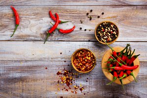 Red hot chilli pepper pods in a wooden mortar, pepper flakes and peppercorns in wooden bowls