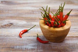 Red hot pepper pods in a wooden mortar and pepper pods on wooden table